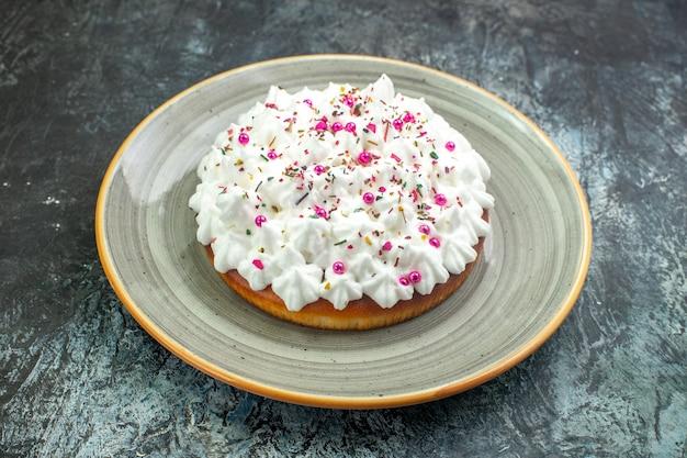 Vue de dessous gâteau avec crème pâtissière sur plateau rond gris sur table grise