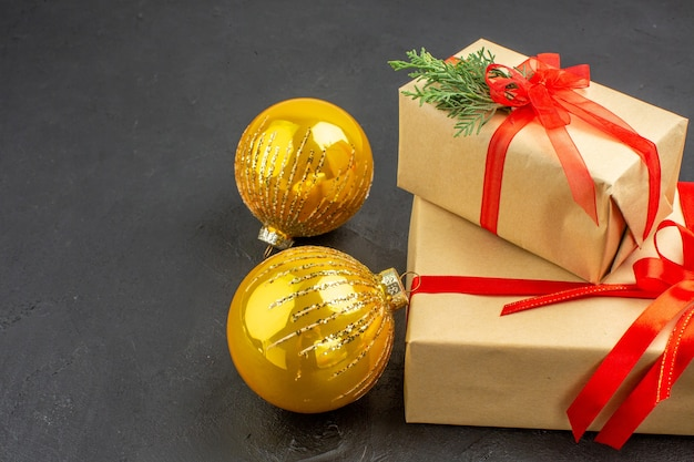 Vue de dessous grands et petits cadeaux de noël en papier brun attaché avec des boules de noël en ruban rouge sur fond sombre