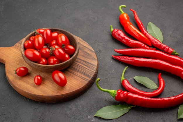 Vue de dessous gros plan poivrons rouges et payer les feuilles et un bol de tomates cerises sur la planche à découper ovale sur tableau noir