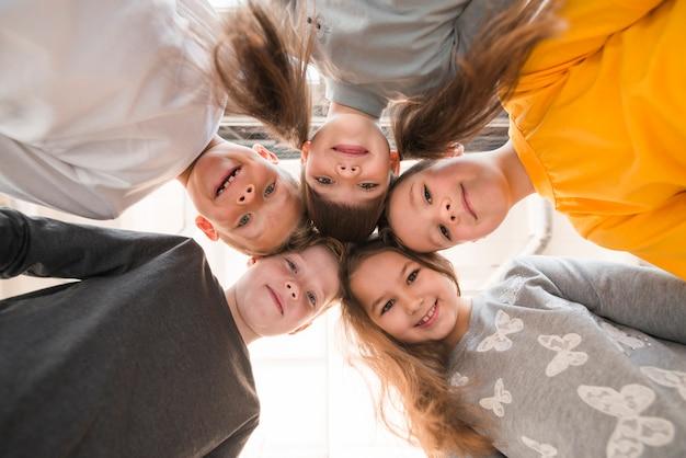 Vue de dessous groupe d'enfants posant ensemble
