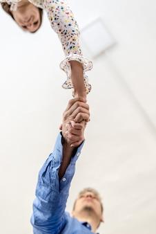 Vue de dessous d'un homme d'affaires et d'une femme serrant la main conceptuelle d'un accord ou d'un partenariat avec espace de copie sur un plafond blanc.