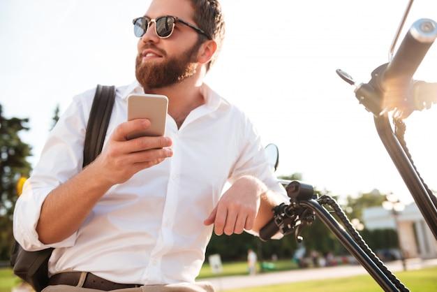 Vue de dessous d'un homme barbu souriant à lunettes de soleil assis sur une moto moderne à l'extérieur et tenant un smartphone tout en regardant ailleurs