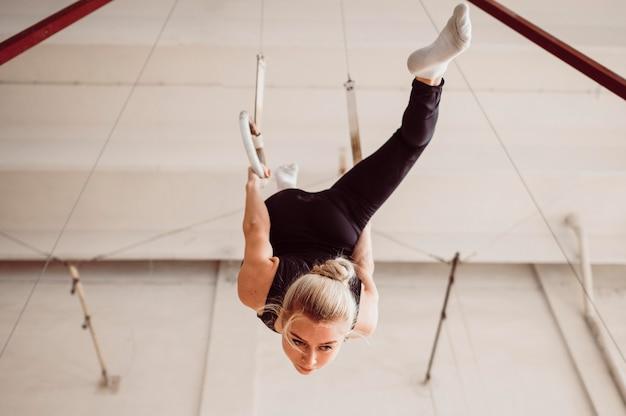 Vue de dessous jeune femme formation sur les anneaux de gymnastique