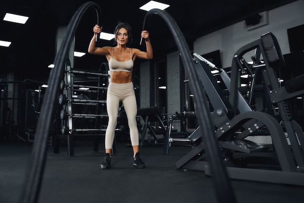 Vue de dessous de la jeune sportive brune en sportswear beige formation dans une salle de sport vide avec des cordes