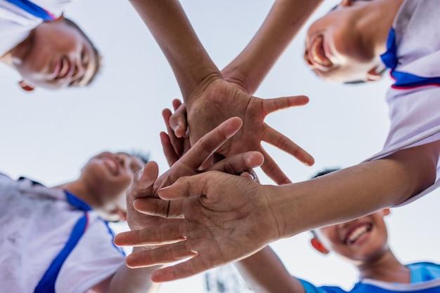 Vue de dessous de jeunes joueurs de football garçon réunissant les mains avant le match