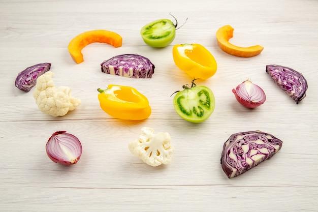Vue de dessous légumes coupés chou rouge chou-fleur poivron jaune tomate verte oignon rouge sur une surface en bois blanche