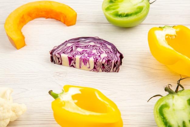 Vue de dessous légumes coupés chou rouge tomate verte citrouille poivron jaune sur une surface en bois blanche