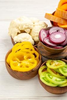 Vue de dessous légumes coupés citrouille coupés poivrons jaunes coupés oignon coupé tomates vertes chou-fleur dans des bols sur une surface en bois