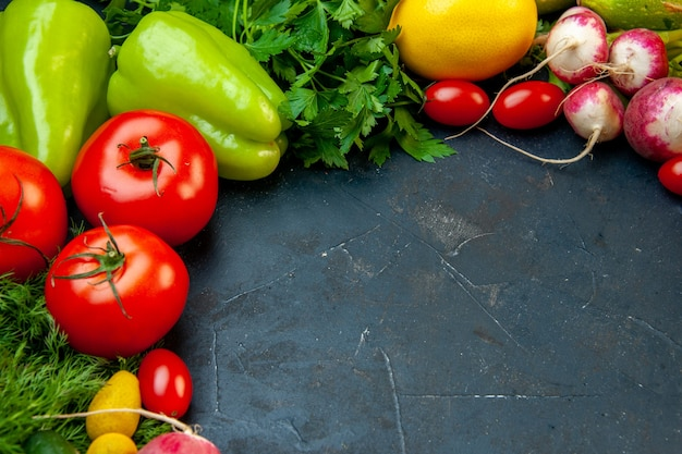Vue de dessous légumes frais tomates radis persil aneth tomates cerises poivrons citron sur une surface sombre avec copie place