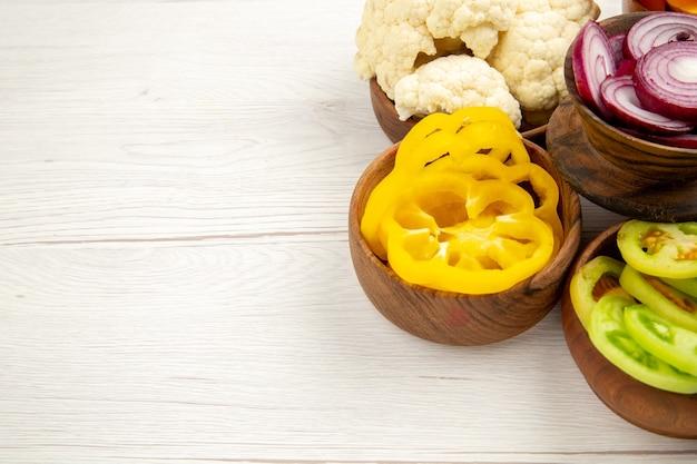 Vue de dessous des légumes hachés coupés des oignons coupés des tomates vertes du chou-fleur des poivrons jaunes coupés dans des bols sur une table blanche avec un espace libre