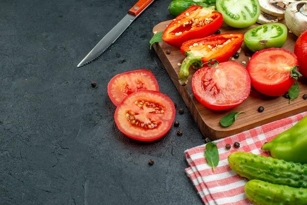 Vue de dessous légumes tomates poivrons sur planche à découper verts dans un bol concombres sur nappe rouge couteau sur table noire copie place