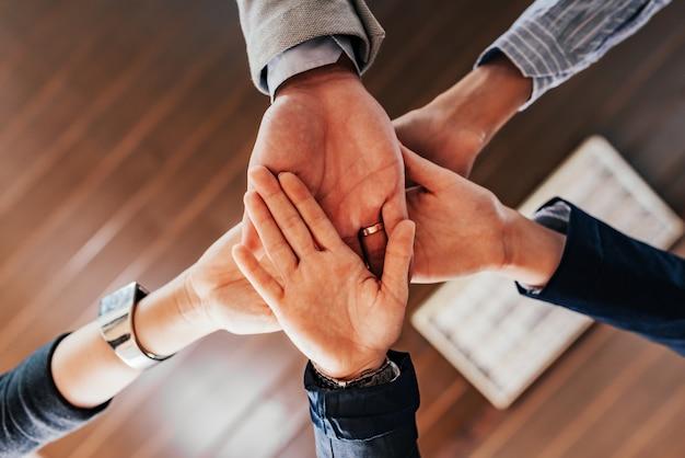 Vue de dessous des mains de personnes tenant ensemble.