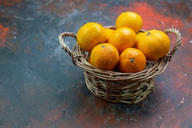Vue de dessous mandarines fraîches dans un panier en osier sur une table rouge foncé avec espace libre