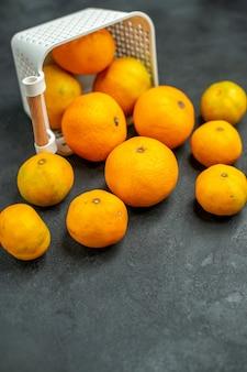 Vue de dessous des mandarines et des oranges éparpillées du panier en plastique sur un espace libre sombre