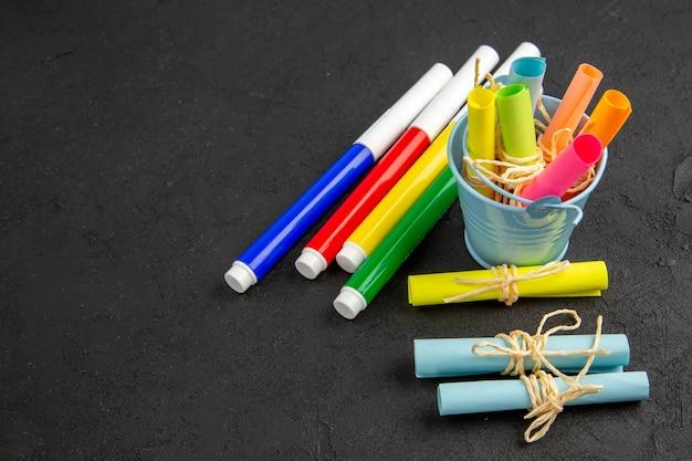 Vue de dessous des marqueurs de couleur enroulés des notes autocollantes attachées avec une corde dans un petit seau sur un espace libre de table noire