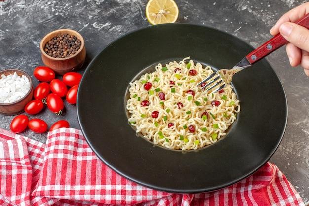 Vue de dessous nouilles ramen asiatiques sur fourche noire dans des tomates cerises citron coupées à la main sel de mer poivre noir dans de petits bols sur une table sombre