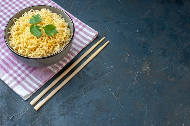 Vue de dessous nouilles ramen dans un bol sur des baguettes d'essuie-tout à carreaux roses et blancs sur un endroit libre de table sombre