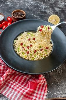 Vue de dessous nouilles ramen soulevées sur fourche sur plaque noire poivre noir dans un bol tomates cerises au citron coupées sur table sombre