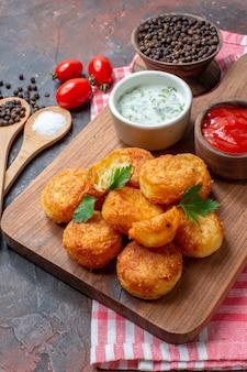 Vue de dessous nuggets de poulet sur planche de bois avec sauces tomates cerises cuillères en bois poivre noir dans un bol sur fond sombre