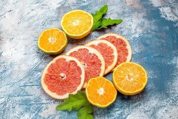 Vue de dessous des oranges et des pamplemousses coupés sur une surface blanche bleue