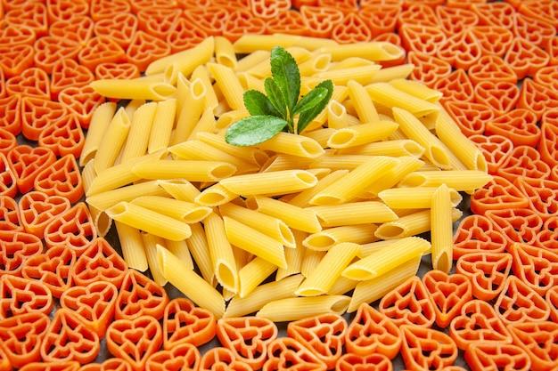 Vue de dessous des pâtes italiennes en forme de coeur et des penne sur une surface sombre