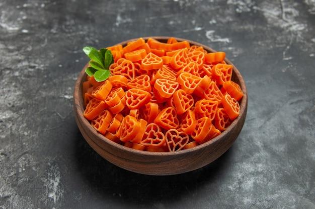 Vue de dessous des pâtes italiennes rouges en forme de coeur dans un bol sur une surface sombre