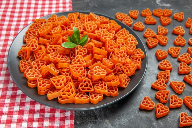 Vue de dessous des pâtes italiennes rouges en forme de coeur sur une plaque ovale noire sur une serviette de cuisine des pâtes au coeur éparpillées sur une table sombre