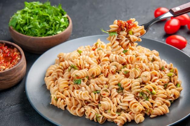 Vue de dessous des pâtes rotini sur une assiette sur une fourchette, des tomates cerises, de la sauce tomate et des légumes verts hachés dans des bols sur une surface isolée sombre