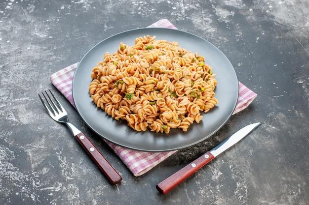 Vue de dessous des pâtes rotini sur une assiette ronde sur une fourchette et un couteau à serviette à carreaux blancs roses sur une table grise