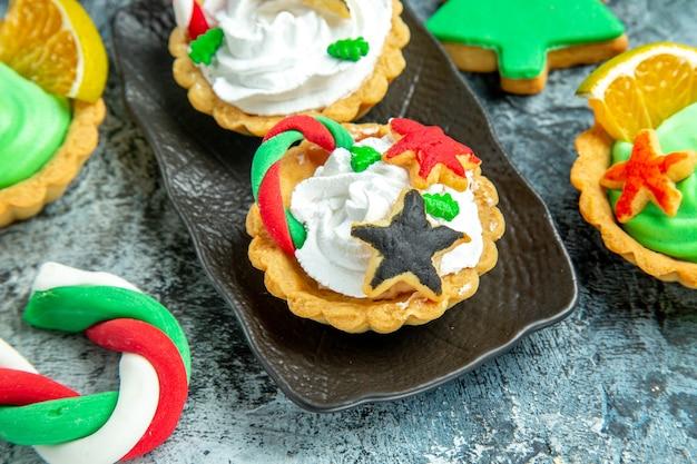 Vue de dessous petites tartes de noël sur plaque noire bonbons de noël et biscuit sur table grise