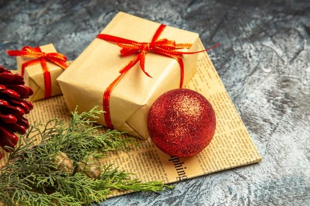 Vue de dessous de petits cadeaux attachés avec une branche de pin de boule de noël de ruban rouge sur un journal sombre
