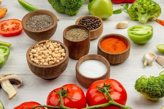 Vue de dessous des pois aux yeux noirs et des épices différentes dans de petits bols de légumes coupés sur une table grise