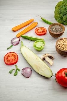 Vue de dessous les pois aux yeux noirs et le poivre noir dans de petits bols coupent des légumes sur un tableau blanc