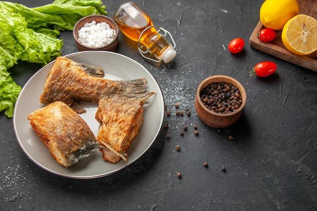 Vue de dessous poisson frit sur assiette laitue poivre noir et sel de mer dans des bols tomates cerises citrons sur planche de bois sur tableau noir