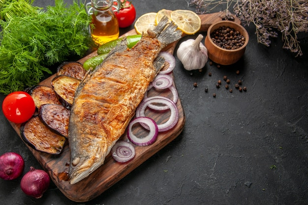 Vue de dessous poisson frit aubergines oignon sur planche de service en bois bol de poivre noir bouteille d'huile aneth sur fond sombre