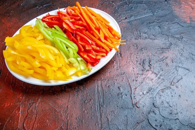 Vue de dessous des poivrons coupés colorés sur une plaque blanche sur un espace libre de table rouge foncé