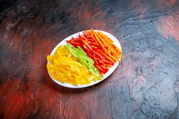 Vue de dessous des poivrons coupés colorés sur une plaque blanche sur un lieu libre de table rouge foncé