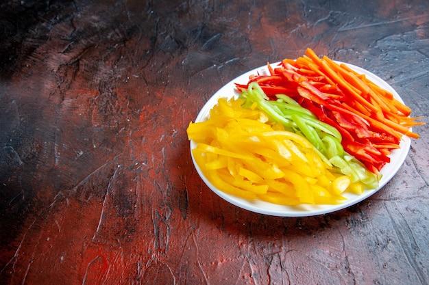 Vue de dessous poivrons coupés colorés sur plaque blanche sur table rouge foncé avec espace libre