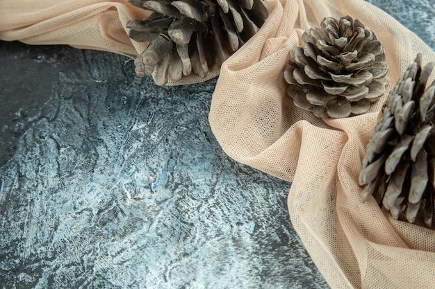 Vue de dessous des pommes de pin sur un châle beige sur un espace de copie de surface sombre