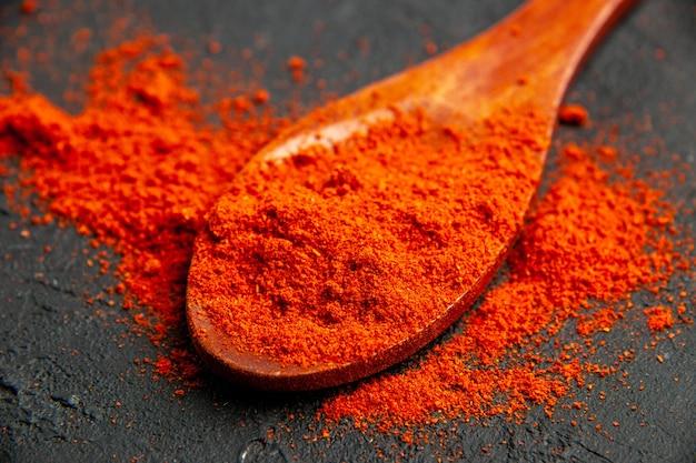 Vue de dessous de la poudre de poivron rouge sur une cuillère en bois sur une table noire