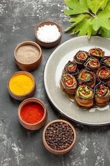 Vue de dessous des rouleaux d'aubergines farcies sur une assiette ovale blanche différentes épices dans de petits bols sur fond gris