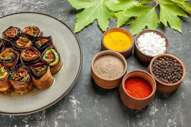 Vue de dessous des rouleaux d'aubergines farcies dans une assiette blanche différentes épices sur fond gris