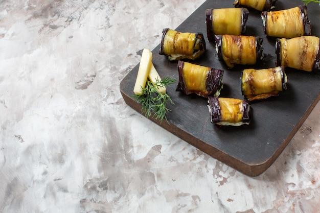 Vue de dessous des rouleaux d'aubergines grillées sur une planche à découper en bois sur fond abstrait