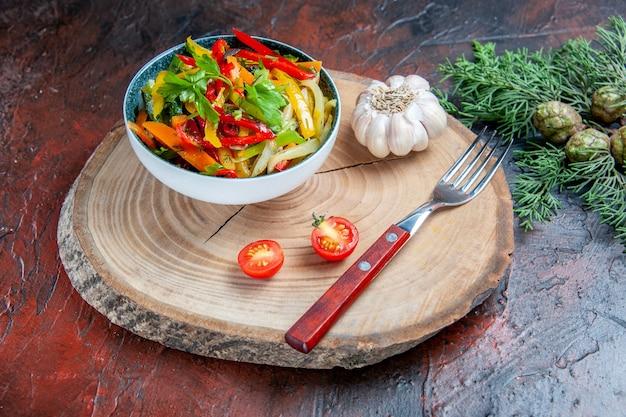 Vue de dessous salade de légumes dans un bol fourchette à l'ail sur une branche de sapin rustique sur une table rouge foncé
