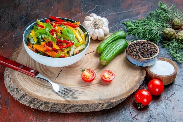 Vue de dessous salade de légumes dans un bol fourchette ail poivre noir concombres sur une branche de sapin rustique sur table rouge foncé