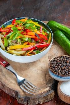 Vue de dessous salade de légumes dans un bol fourchette de concombres poivre noir sur planche rustique sel sur table rouge foncé