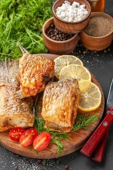 Vue de dessous de savoureux poissons frits tranches de citron coupées de tomates cerises sur une planche à découper différentes épices dans des bols sur fond noir