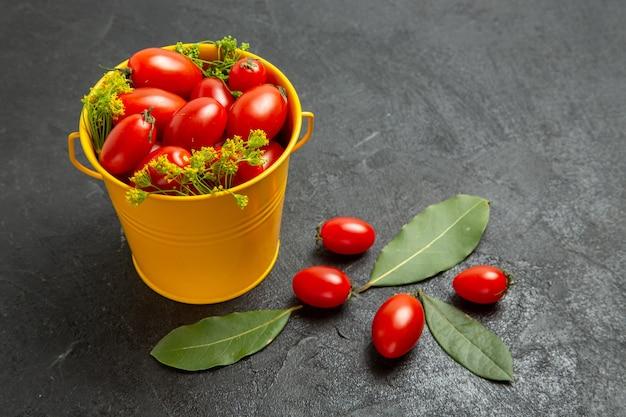 Vue de dessous seau jaune de tomates cerises et de fleurs d'aneth et de feuilles de laurier sur le fond sombre