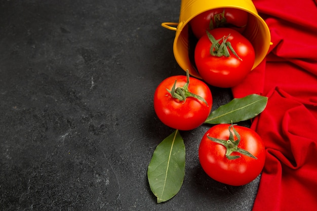 Vue de dessous seau avec serviette rouge tomates rouges sur fond sombre