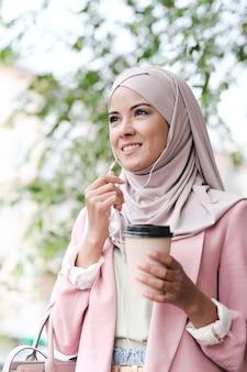 Vue de dessous de sourire confiant jeune femme d'affaires arabe en hijab, boire du café et utiliser des écouteurs tout en répondant au téléphone en mouvement
